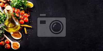 Fototapeta Food background. Top view of olive oil, cherry tomato, herbs and spices on rustic black slate. Colorful food ingredients border.