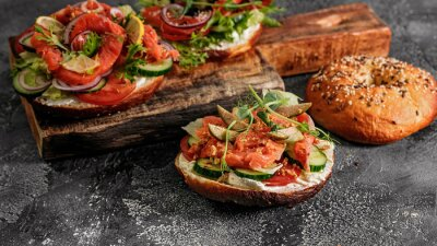 Fototapeta Food banner sandwich salad New York bagel with cream cheese, lettuce, cucumber, capers, onions and salted red fish. Excellent delicious breakfast or snack on cutting board. Copy space