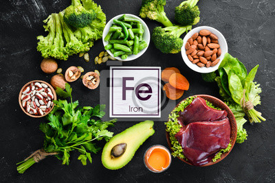 Fototapeta Food containing natural iron. Fe: Liver, avocado, broccoli, spinach, parsley, beans, nuts, on a black stone background. Top view.