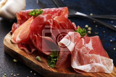 Food tray with delicious salami, coppa, crudo and herbs. Meat platter with selection on rustic table