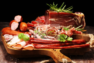 Food tray with delicious salami, pieces of sliced ham, sausages,salad and vegetable. Meat platter with selection