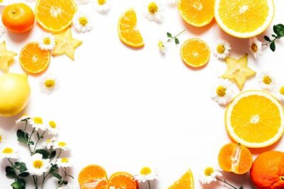 Fototapeta Frame of sliced oranges and tangerines with flowers on white background, copy space