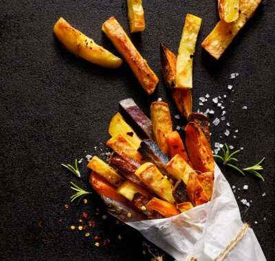 Fototapeta French fries,  baked fries from different types and colors of potatoes sprinkled with herbs and spices in paper bag on a black background, top view, close-up.