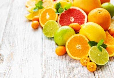 Fototapeta Fresh citrus fruits on an old wooden background
