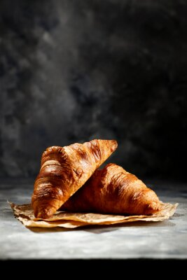 Fresh croissant on dark mood background and copy space for your product.