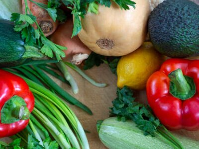Fototapeta Fresh crop of vegetables laid out on a wooden table. Zucchini, pumpkin, bell peppers, herbs, lemons and avocados make up the colorful background.