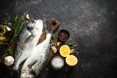 Fototapeta Fresh fish dorado on black stone table.