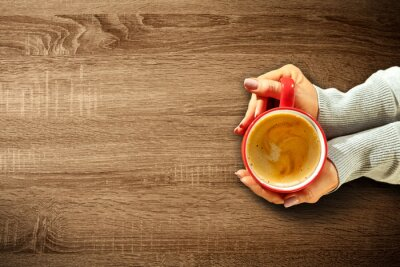 Fresh hot coffee in woman hands and wooden table of free space for your decoration.