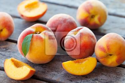 Fototapeta Fresh peaches, fruits on grey wooden background. Close up.