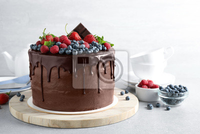 Fototapeta Freshly made delicious chocolate cake decorated with berries on white table