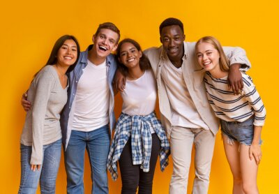 Fototapeta Friendly group of international students smiling over yellow background
