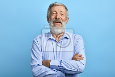 Fototapeta friendly handsome man standing with crossed arms, laughing at something, looking at the camera. close up photo.happiness, feeling and emotion