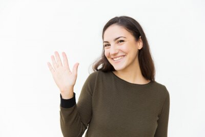 Fototapeta Friendly happy beautiful woman waving hello at camera. Young woman in casual standing isolated over white background. Greeting concept