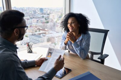 Fototapeta Friendly interview between Indian businessman hr director holding paper cv hiring for job female African American applicant manager sitting in contemporary office. Human resources recruitment concept.
