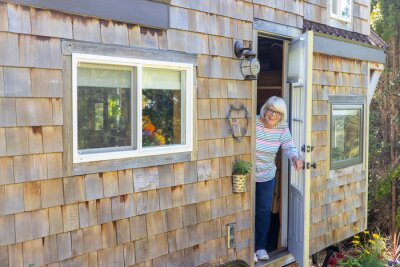 Fototapeta Friendly mature woman standing at front door of her charming little wooden tiny home or house