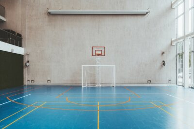 Fototapeta Front view of the court in the gymnasium hall; an indoor modern office stadium with a basketball basket and hoop, football goal, blue floor, a concrete wall with an undeployed projection screen above