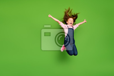 Fototapeta Full length photo of cheerful pretty little schoolchild jumping high rejoicing summer holidays hair flying wear casual denim overall pink shirt isolated green background