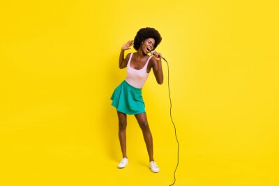 Fototapeta Full size photo of pretty afro american charming woman wear pink singlet good singer karaoke isolated on yellow color background