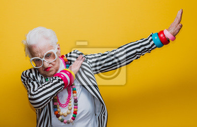 Fototapeta Funny grandmother portraits. Senior old woman dressing elegant for a special event. granny fashion model on colored backgrounds