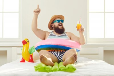 Fototapeta Funny guy in sunglasses, sun hat and swim ring sitting on beach mattress and sipping cocktail points finger up struck by cool idea on how to turn quarantine holiday at home into fun summer vacation