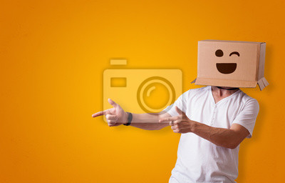 Fototapeta Funny man wearing cardboard box on his head with smiley face