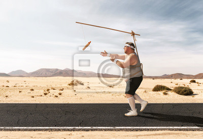 Fototapeta Funny overweight man chasing the hot dog on the stick through the empty road with copy space