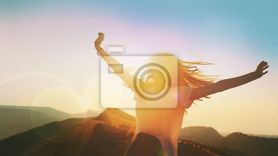 Fototapeta Girl on a background of mountains joyful spread her arms dancing at a height