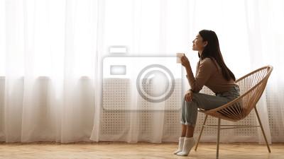 Fototapeta Girl Sitting in Armchair And Enjoying Coffee