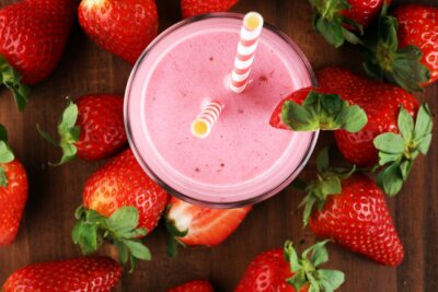Glass of fresh strawberry shake, smoothie or milkshake and fresh strawberries on table. Healthy food and drink concept