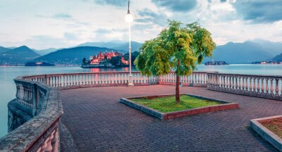 Fototapeta Gloomy evening cityscape of Stresa town. Wonderful summer view of Maggiore lake with Bella island on background, Province of Verbano-Cusio-Ossola, Italy, Europe. Traveling concept background.
