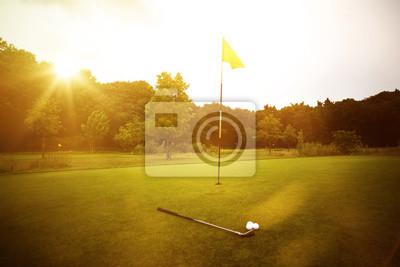 Fototapeta Golfplatz w Abendrot mit Loch und Golfball und Fahne