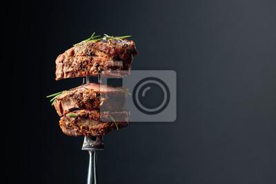 Fototapeta Grilled ribeye beef steak with rosemary on a black background.