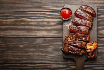 Fototapeta Grilled/fried and sliced marbled meat steak with fork, tomatoes, tomato sauce/ketchup on wooden cutting board, top view, close-up with space for text, rustic background. Beef meat steak concept