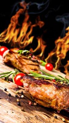 Fototapeta Grillowane steki wołowe z płomieni na tle