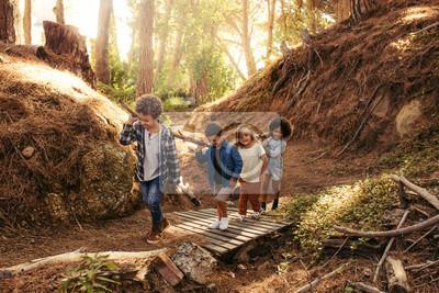 Fototapeta Group of children building camp in forest
