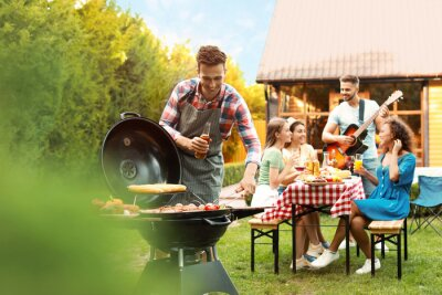 Fototapeta Group of friends at barbecue party outdoors. Young man near grill