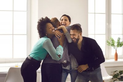 Fototapeta Group of overjoyed young diverse people hugging each other. Team of excited office workers and friends embracing their colleague congratulating him on promotion or happy life event