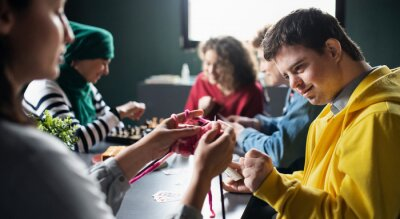 Fototapeta Group of people playing cards and board games in community center, inclusivity of disabled person.