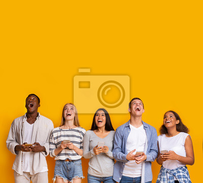Fototapeta Group of surprised students with smartphones over yellow background