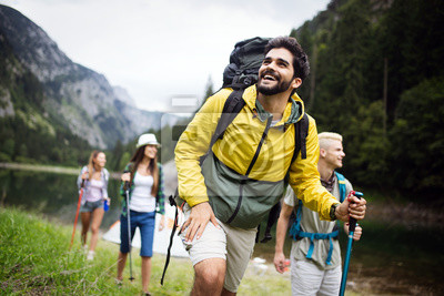 Fototapeta Group of young friends hiking in countryside. Multiracial happy people travelling in nature