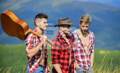 Fototapeta Group of young people in checkered shirts walking together on top of mountain. Men with guitar hiking on sunny day. Tourists hiking concept. Hiking with friends. Long route. Adventurers squad