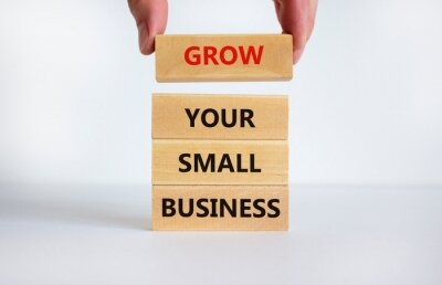 Fototapeta Grow your small business symbol. Words 'grow your small business' on wooden blocks. Businessman hand. Beautiful white background. Grow your small business concept, copy space.
