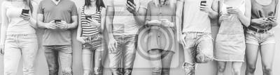 Fototapeta Grupa przyjaciół nastolatek oglądania inteligentnych telefonów komórkowych