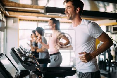 Fototapeta Grupa sportowa ludzi na siłowni. Koncepcje dotyczące stylu życia i sportu w klubie fitness
