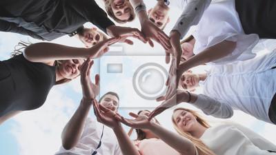 Fototapeta Grupa uczniów szkół średnich patrzy przez kształt koła utworzonego z ich dłoni. Pojęcie przyjaznych przyjaciół.