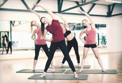 Fototapeta grupa uśmiechniętych kobiet, rozciągając w siłowni