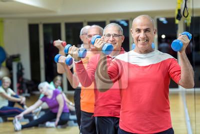 Fototapeta Grupo di uomini in fila fa gli esercizi con dei manubri colorati in una sala di una palestra