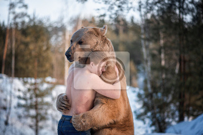 Fototapeta Half-naked man hugs a brown bear in a winter forest. Bear hugs man in response. The theme of the friendship of man and animal.