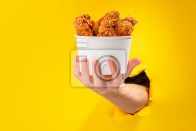 Fototapeta Hand giving chicken nuggets