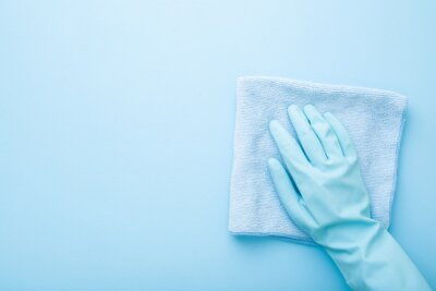 Fototapeta Hand in rubber protective glove wiping table, wall or floor surface in kitchen, bathroom or other room. Closeup. Empty place for text or logo. Light pastel blue background. Top down view.
